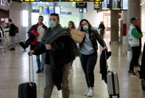 Travelers coming from Italy arrive at Manises airport with facial masks, in Valencia, eastern Spain, 25 February 2020. Two men who were recently in Milan are under inquiry at Vila-Real's Plana Hospital for a possible coronavirus infection. EFE/ Biel Alino